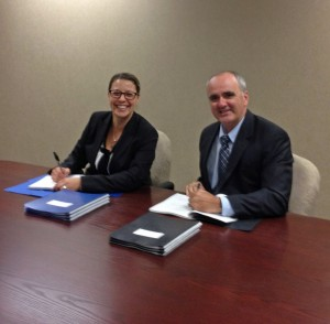 ACFO President Milt Isaacs and Treasury Board Negotiator Karine  Renoux sign the FI Collective Agreement on Sept. 30, 2013.